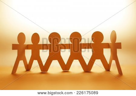 Team of paper chain people in a row holding hands