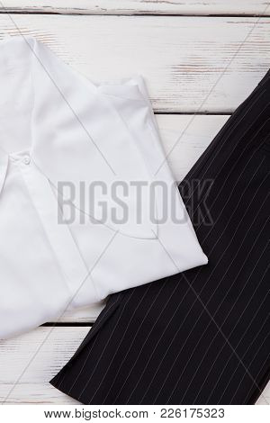 Women Office Style Apparel. Female White Formal Style Blouse And Black Skirt, White Wooden Backgroun