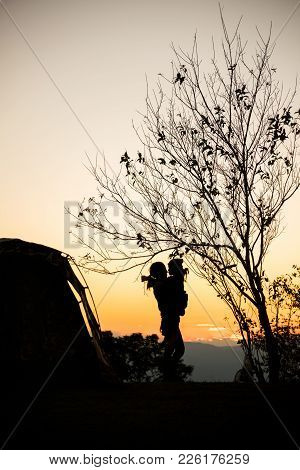 Silhouette Of Mother With Her Daughter Embrace Hug Near The Tent And Tree At Sunset, Camping In The