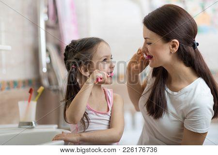 Little Kid Girl And Mom Brushing Teeth In Bathroom