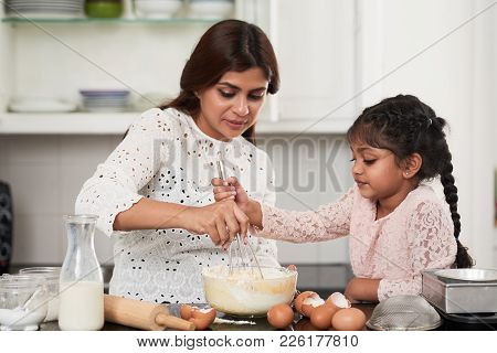Cute Indian Girl Helping Her Beautiful Middle-aged Mother To Beat Eggs And Flour With Whisk While Ma