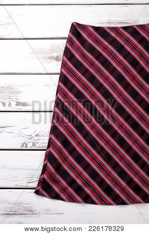 Classic Red Striped Skirt. Female Colorful Skirt On White Wooden Background. Feminine Fashion Outfit