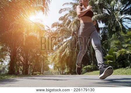 Young Fitness Sport Woman Running On The Road In The Morning, Sun Light Flare , Selective Focus.