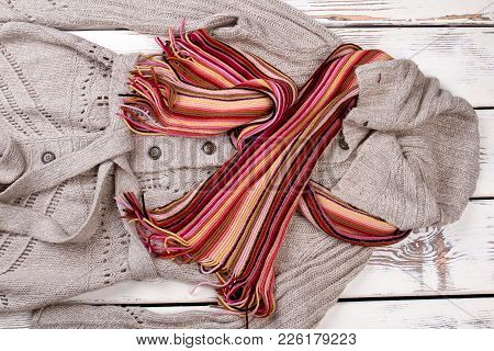 Female Gray Cardigan And Scarf. Women Fashion Autumn Outfit On Wooden Background. Feminine Fashion A