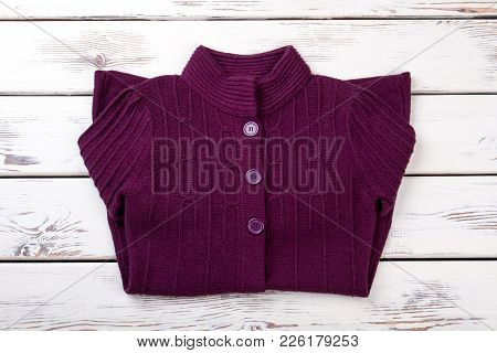 Warm Purple Sweater For Women. Female Knitted Cardigan Folded On White Wooden Background. Feminine A