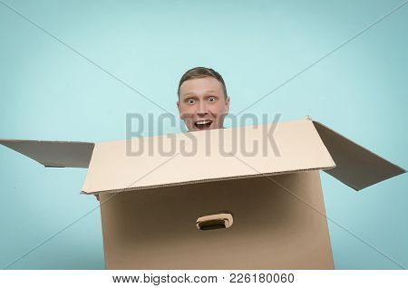 Happy Exited Man Is Holding In Hands A Big Cardboard Box In Front Of Him Isolated On Blue Background