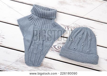 Set Of Female Knitted Hat And Scarf. Stylish Feminine Blue Knit Snood And Cap, White Wooden Backgrou