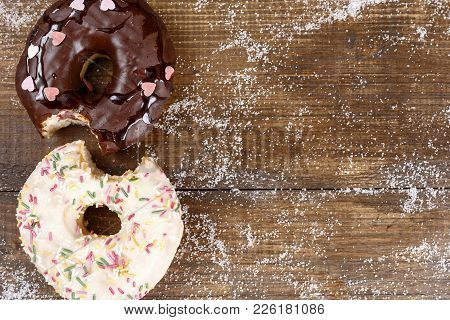 Two Bitten Donuts With Glaze And Chocolate On A Dark Wooden Surface Top View Copy Space. American Na