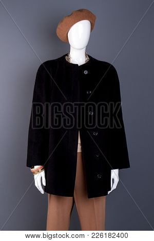 Female Mannequin Dressed In Black Coat. Brown Women Beret And Trousers On Mannequin, Grey Background