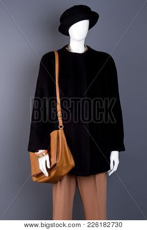 Female Mannequin With Leather Fashion Handbag. Brown Trousers, Black Coat And Hat On Women Mannequin