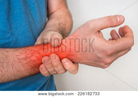Man With Wrist Pain Is Holding His Aching Hand - Body Pain Concept