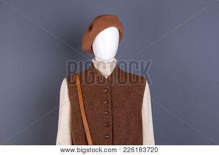 Women Brown Wool Beret And Waistcoat. Turtleneck Sweater And Warm Waistcoat On Mannequin, Grey Backg