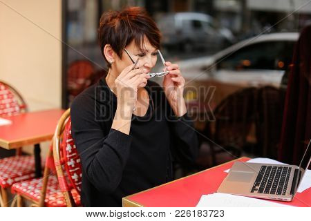 Aged Grandmother Sitting With Laptop In Outdoor Cafe And Have Conversation  With Grandchildren By Vi