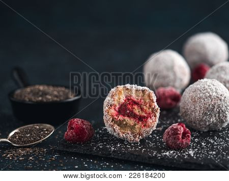 Raw Vegan Lamington Bliss Balls With Raspberries Chia Jam On Dark Background. No Baked Healthy Vegan