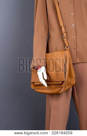 Female Mannequin With Fashion Brown Handbag. Dummy Clothed In Brown Formal Shirt And Trousers, Cropp