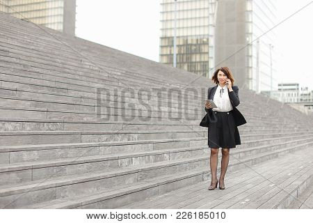 Asian Appearance Business Woman Walk Along Broad Stairs By   And Smiling Speaking By Phone. In Hand