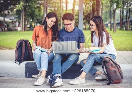 Three Asian Young Campus Students Enjoy Tutoring And Reading Books Together. Friendship And Educatio