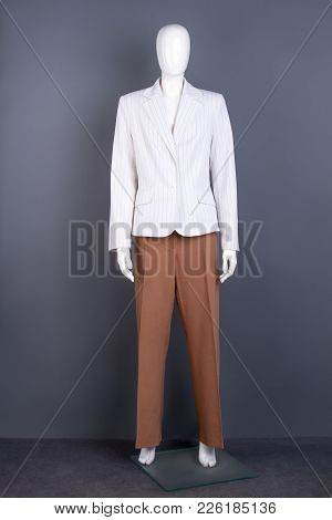 Mannequin In White Blazer And Brown Trousers. White Formal Jacket And Trousers On Female Mannequin.