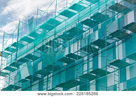 Renovation Of Apartments Building With Scaffolding And Green Safety Net