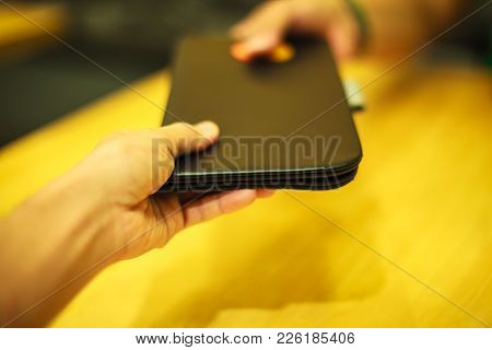 Selective Focus Customer Hand Receive Bill Payment Receipt In Black Leather Folder Holder Tray On Ye