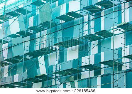 Scaffolding On Building Facade. Fall-protection Safety Net. Building Exterior Renovation.