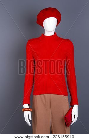Mannequin Dressed In Red Beret And Sweater. Stylishly Clothed Famale Dummy, Grey Background. Ladies