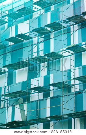 Building Under Construction With Scaffolding And Green Netting On Facade