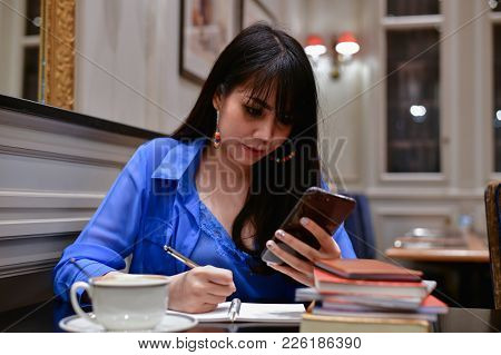 Education Concepts. Asian Women Are Working In A Restaurant. Asian Women Are Reading A Book In A Res
