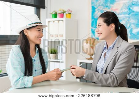 Pretty Smiling Business Woman Introducing Good Travel Plan For Female Customer And Discussing How To