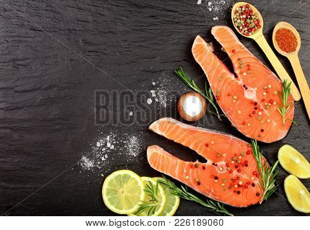 Slice Of Red Fish Salmon With Lemon, Rosemary And Peppercorns On Black Stone Background With Copy Sp