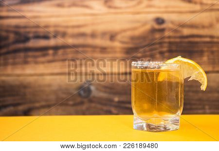 A Tequila With Lemon On An Orange Table And On A Wooden Background