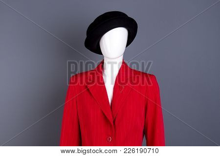 Female Mannequin In Elegant Outfit. Black Hat And Red Blazer On Female Mannequin, Grey Background. L