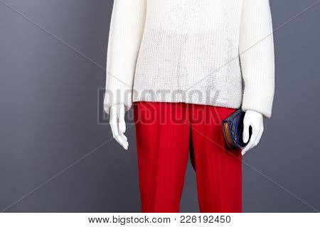 Mannequin In Female Brand Apparel. White Knitted Sweater And Red Trousers For Women, Cropped Image.