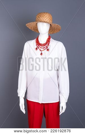 Straw Hat, White Blouse And Necklace. Female Mannequin With White Shirt, Red Trousers, Necklace And