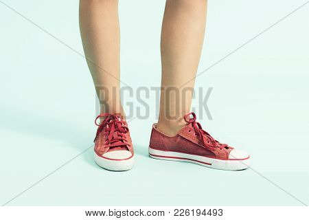 Women Shoes. Sports Shoes , Sneakers. Closeup Of Woman Legs And Feet Wearing Red Shoes.