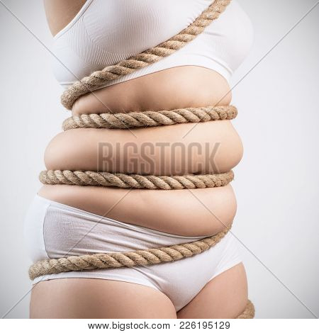 Fat Woman In White Underwear Twisted With A Rope. Obesity Concept. Over Gray Background.