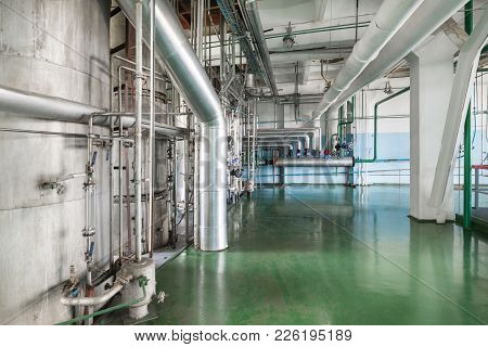 The Rectification Shop. Silvery Distillation Columns Entangled In A Multitude Of Pipes, Valves And S