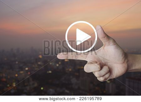 Play Button Icon On Finger Over Blur Of Cityscape On Warm Light Sundown, Business Music Online Conce