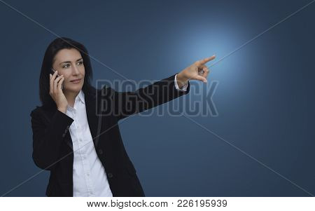 Caucasian Business Woman Talking On Her Cell Phone And Pointing Or Touching Touchscreen Over Gradien