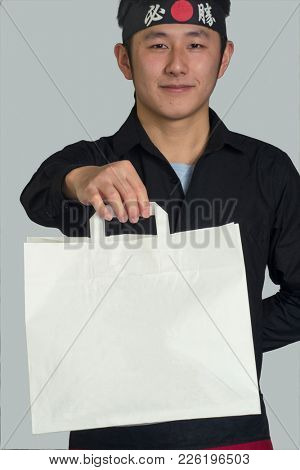 Asian cook hold a take away white bag and wearing a black bandana with Chinese word ( victory )