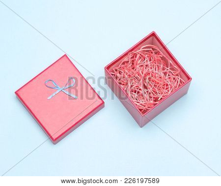 Open Red Gift Box With Decorative Shavings. Close-up, Top View. Gift Packaging