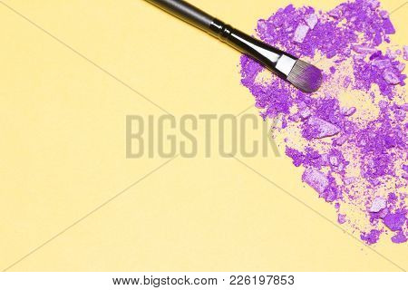 Makeup Brush With Crumbled Mixed Ultra Violet Eye Shadow Different Shades On Yellow. Top View, Selec