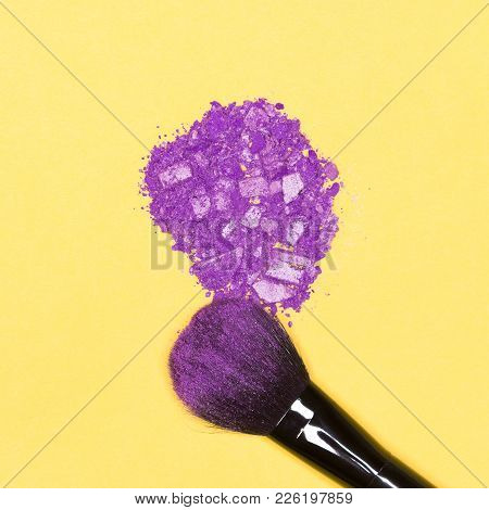 Close-up Of Makeup Brush With Crumbled Violet Eye Shadow On Bright Yellow Background