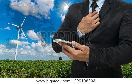 Businessman Using The Smart Phone On Wind Turbine Power Generator On Blue Sky,elements Of This Image