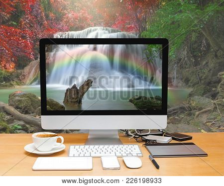 Conceptual Image Of A Workspace With Computer Desktop On Beautiful Waterfall With Soft Focus And Rai