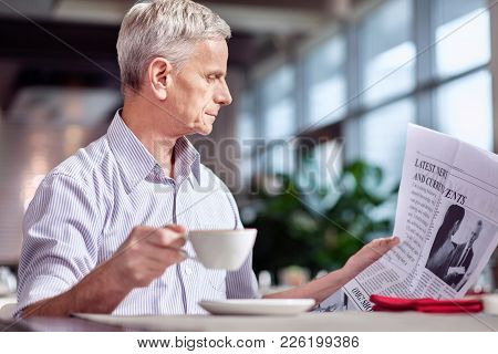 Breaking News. Pleasant Tranquil Mature Man Relaxing While Reading Newspaper And Staring At It