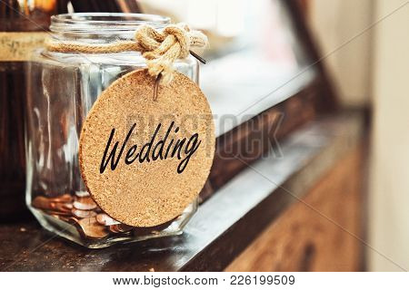 Vintage Retro Glass Jar With Hemp Rope Tie Wedding Tag And Few Coins Inside On Wood Counter Concept