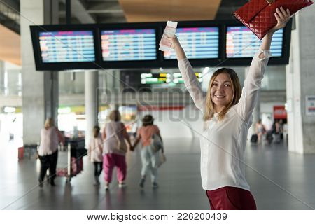 Happy Young Girl With Passport And Ticket Stands And Raised Her Hands Up
