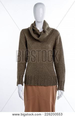 Modern Knitted Sweater For Women. Female Mannequin Dressed In Turtleneck Khaki Pullover And Brown Sk