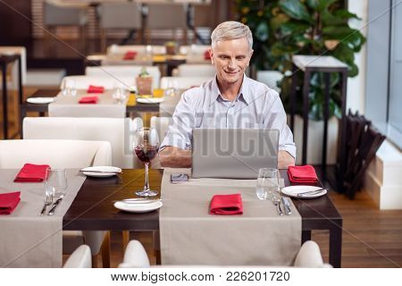Modern Technology. Wistful Attractive Mature Man Sitting At The Restaurant While Typing On Laptop An